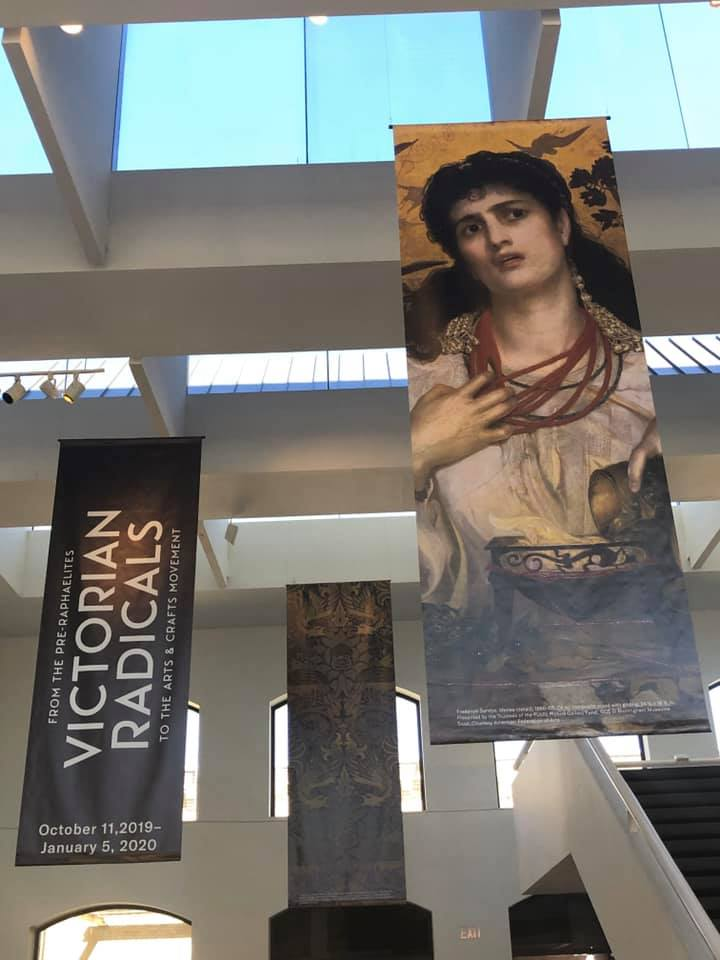 The image shows the interior of the San Antonio Museumn of Art with the exhibition banner for Victorian Radicals: from the Pre-Raphaelites to the Arts & Crafts Movement, as well as a banner showing the image of Medea by Pre-Raphaelite artist Frederick Sandys.