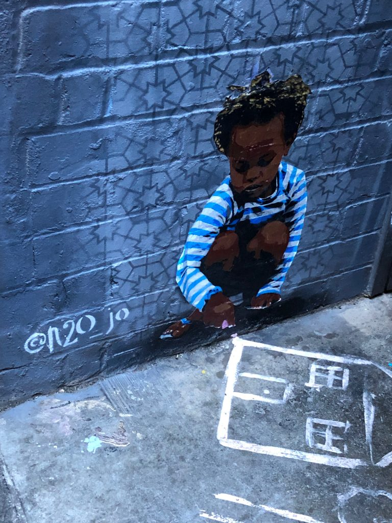 Street art of a child drawing by @n20_jo in Melbourne, Australia