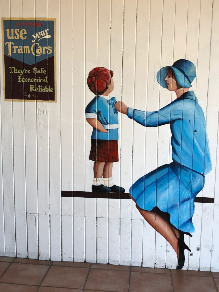 Street art in Napier, New Zealand, depictng a 1920s scene of a woman and child waiting for a tram.